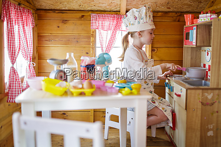 young girl in wendy house pretending