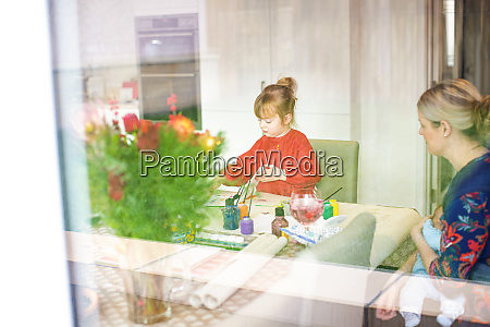 young girl using paints at kitchen