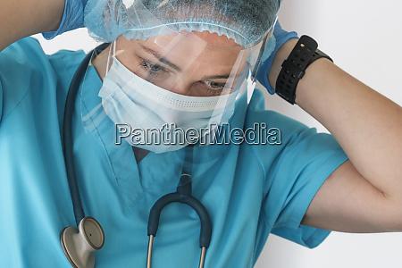 nurse putting on face shield