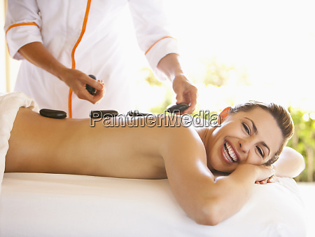 caucasian woman having hot stone massage