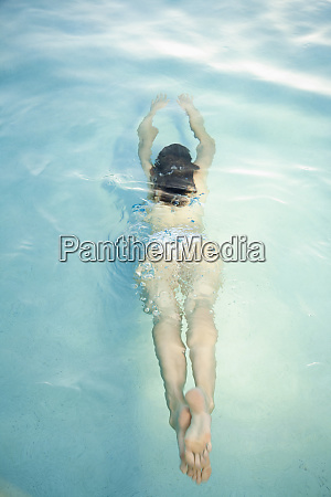 overhead view of woman swimming under