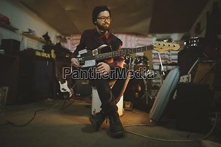 young man playing bass guitar during