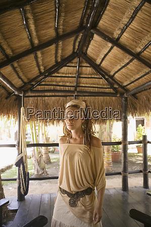 woman standing in straw hut