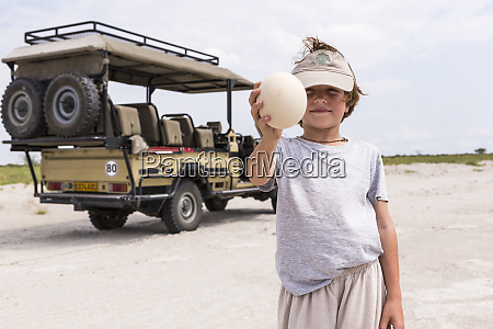 boy holding up a large ostrich