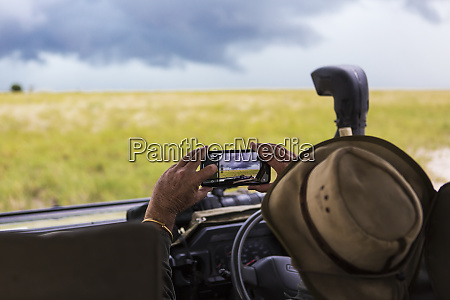 a safari guide taking smart phone