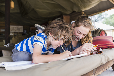 brother and sister doing homework together