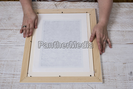 person fitting a picture frame around