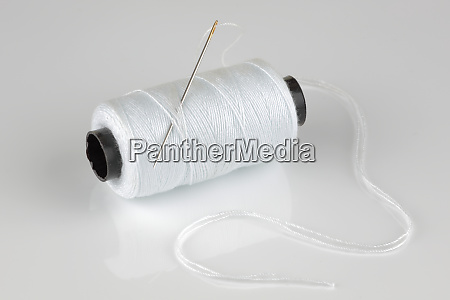 white cotton reel and needle with