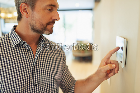 man at touch screen digital thermostat