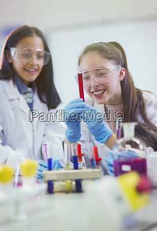 smiling girl students examining liquid in