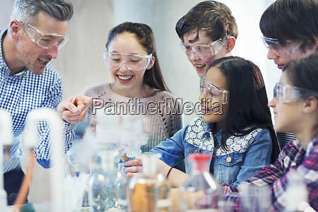 male teacher and students watching chemical