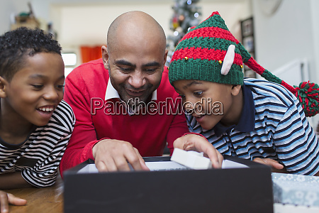 father and sons opening christmas gift