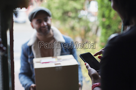 woman signing for package digitally at