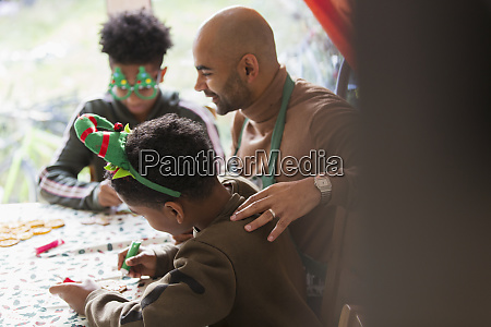 father and sons decorating christmas cookies