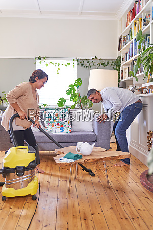 mature couple vacuuming and cleaning living
