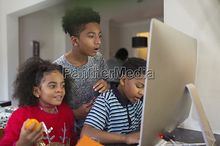 brothers and sister using computer