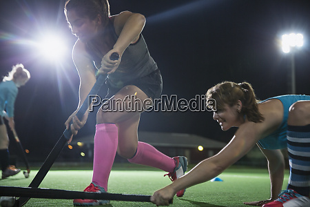 determined female field hockey players playing