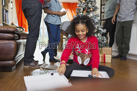 excited girl opening christmas gift on