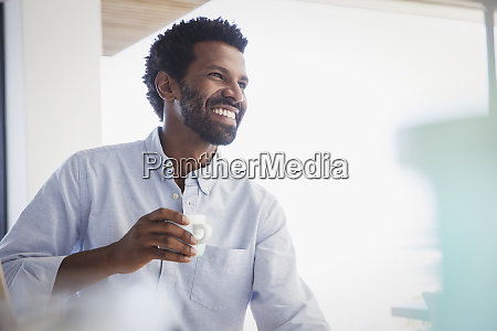 smiling enthusiastic man drinking coffee and