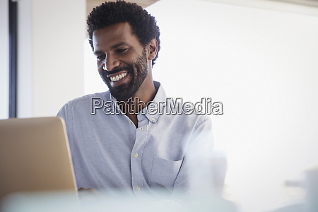 smiling businessman working at laptop