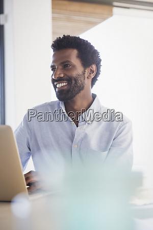 smiling businessman working at laptop