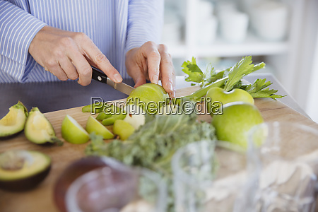 woman cutting healthy green apples and