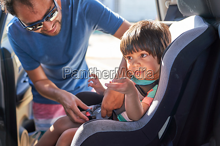 father fastening son in car seat