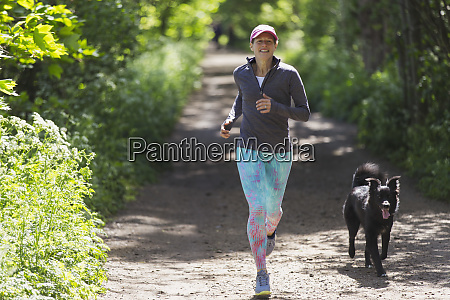 woman jogging with dog on sunny