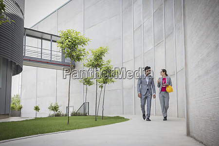 supervisors walking on sidewalk outside factory