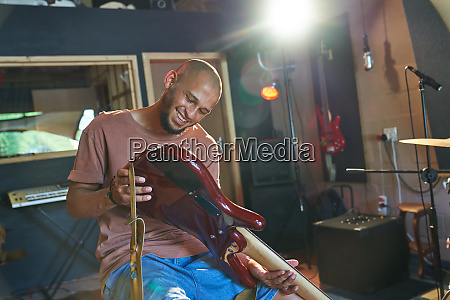 smiling male musician inspecting guitar in