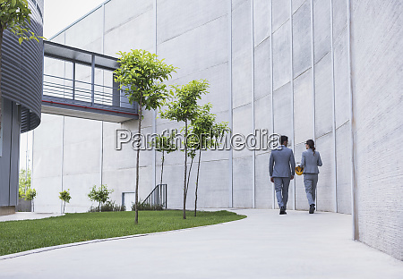 supervisors walking on sidewalk below building
