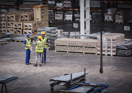 supervisor and workers talking in warehouse