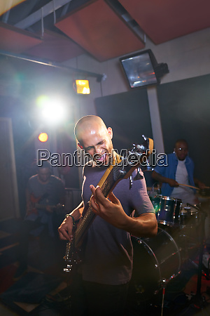 male musician playing guitar in recording