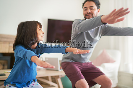 father and daughter exercising doing squats
