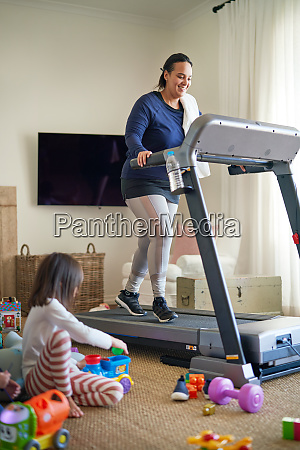 mother exercising on treadmill while daughter