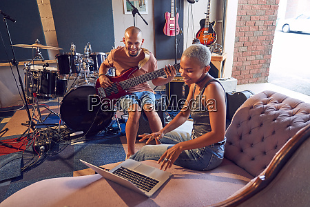 smiling musicians with laptop and guitar