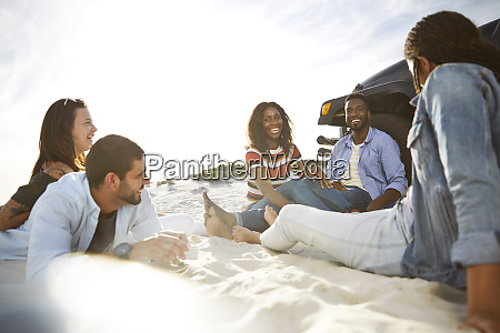 young friends hanging out on beach