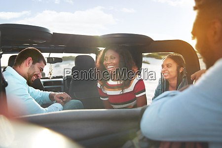 laughing young friends enjoying road trip