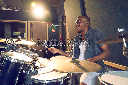 male musician playing drums in recording