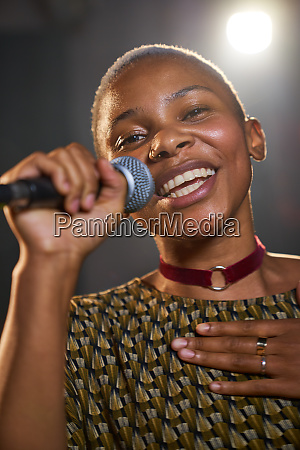 portrait happy young female musician singing