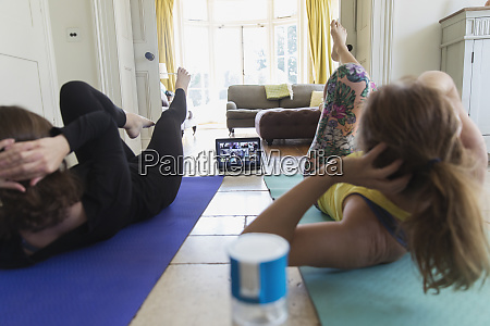mother and daughter taking online yoga