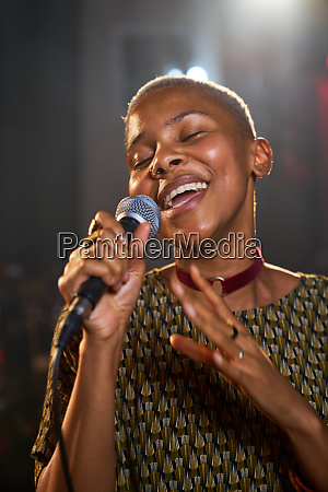 young female musician singing into microphone