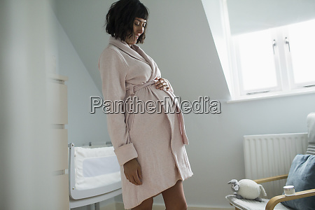 happy pregnant woman in bathrobe rubbing