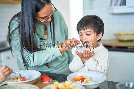 mother feeding son in kitchen