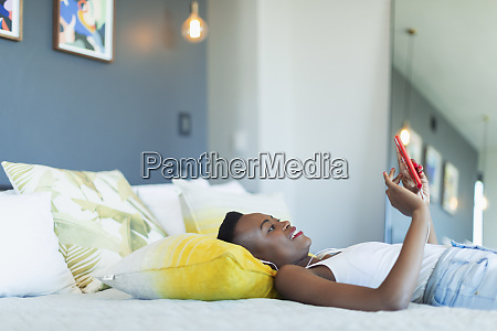 young woman relaxing on bed listening