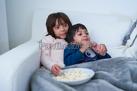 affectionate brother and sister eating popcorn