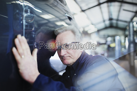 focused male mechanic examining car in