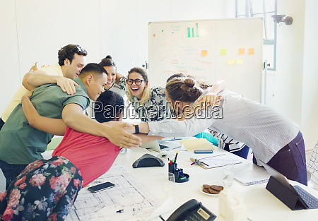enthusiastic architects bonding in huddle in