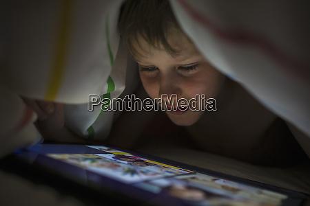 close up boy using digital tablet