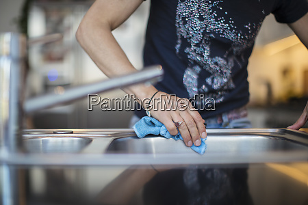 close up woman disinfecting sink